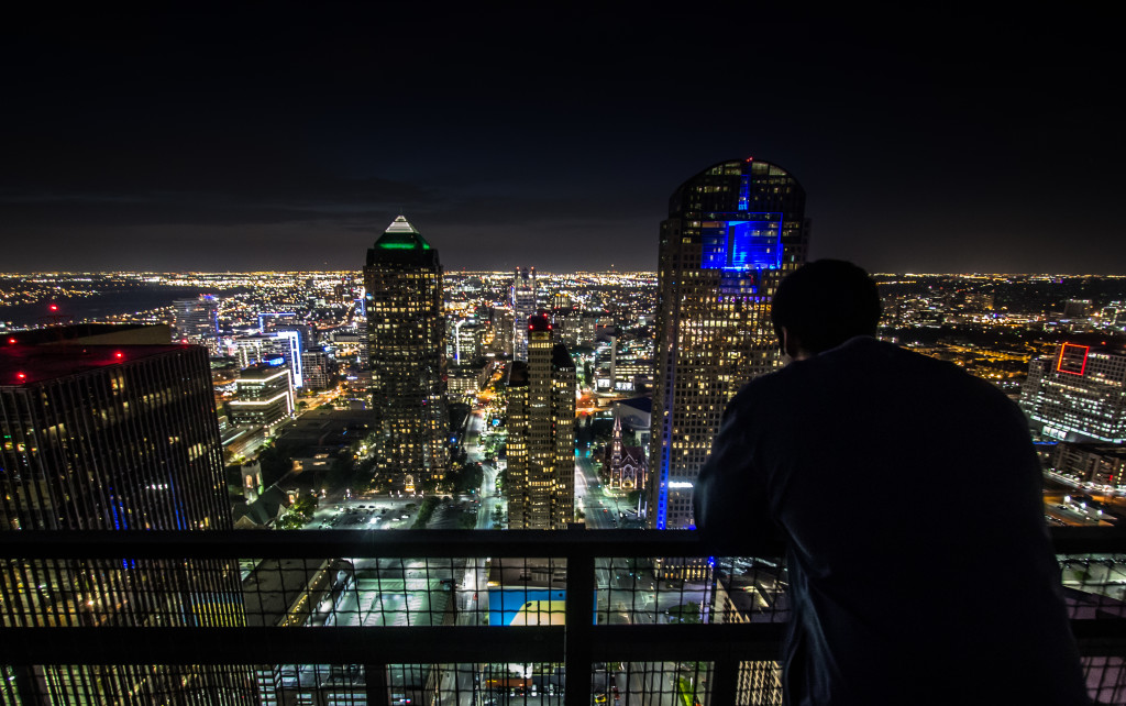 Overlooking downtown Dallas at night from a rooftop.