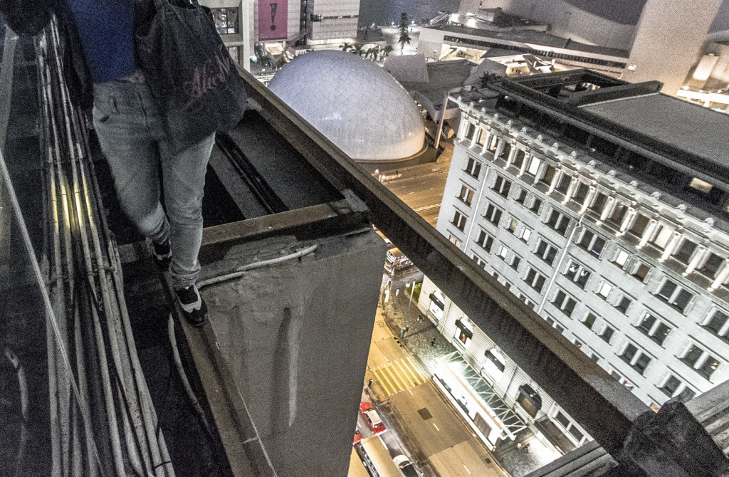 Walking on a beam while rooftopping in Hong Kong