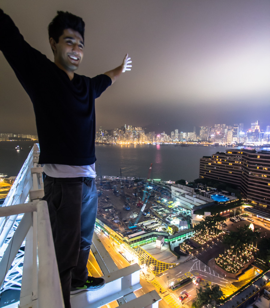 Standing on a giant neon at night; taken while rooftopping in Hong Kong