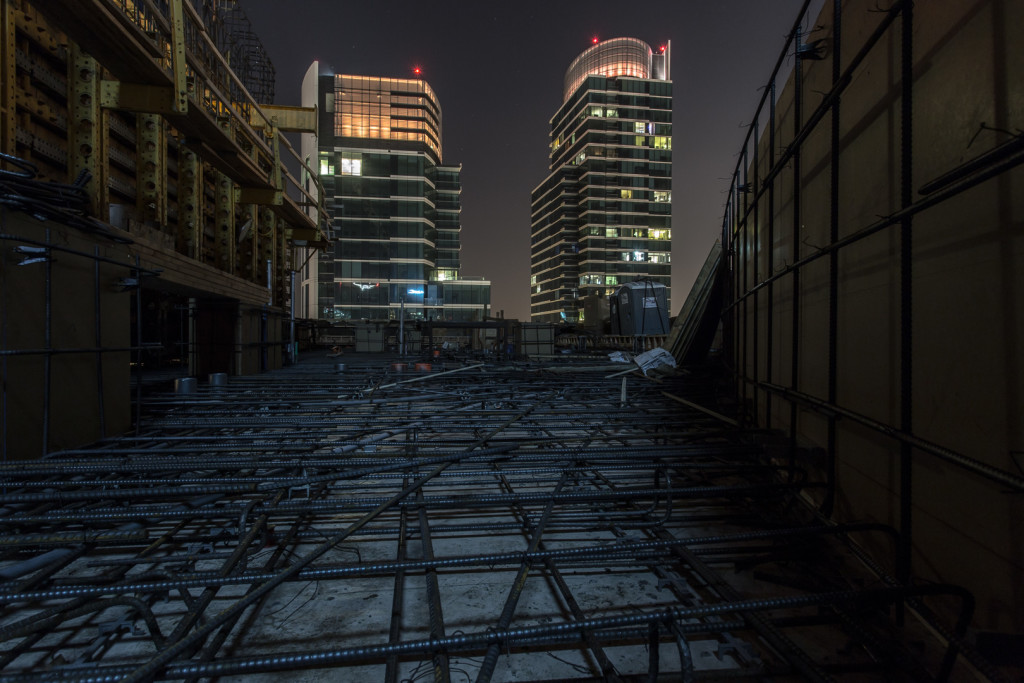 Navigating a metal maze on the top of a construction site at night