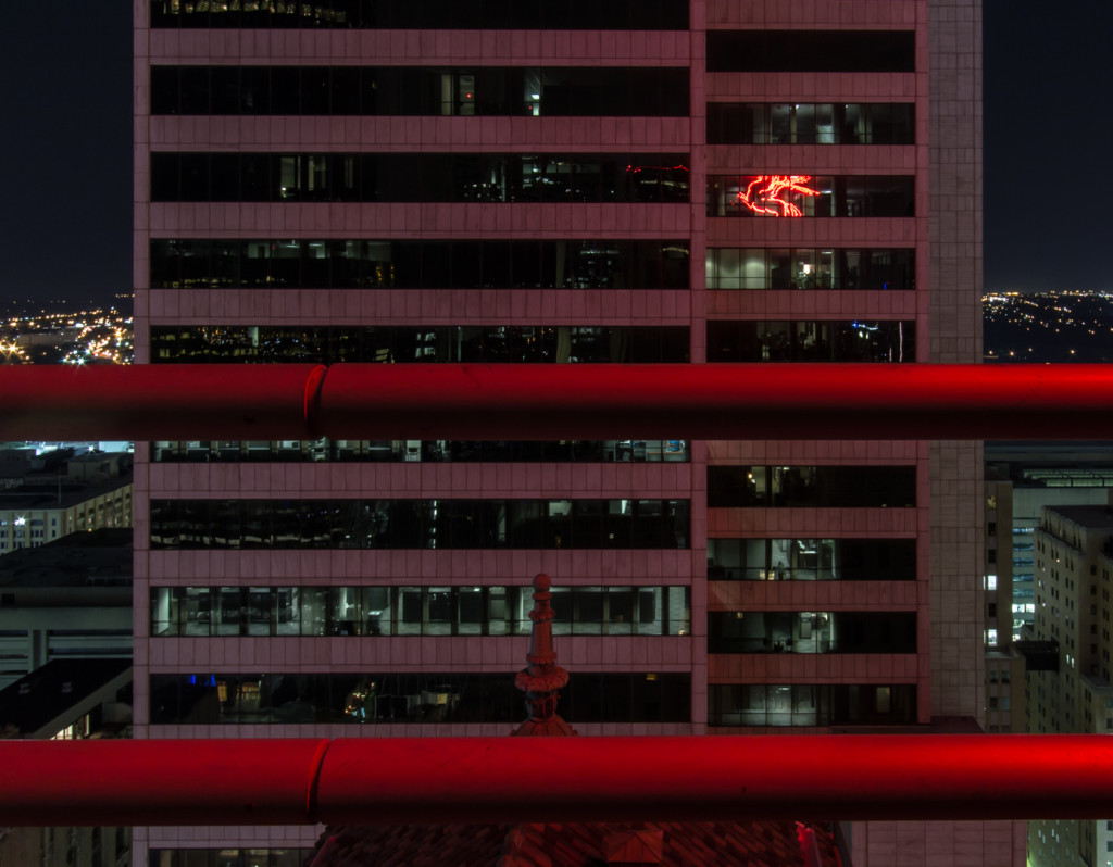 Building at night with 2 bars in the image; taken while rooftopping in Dallas