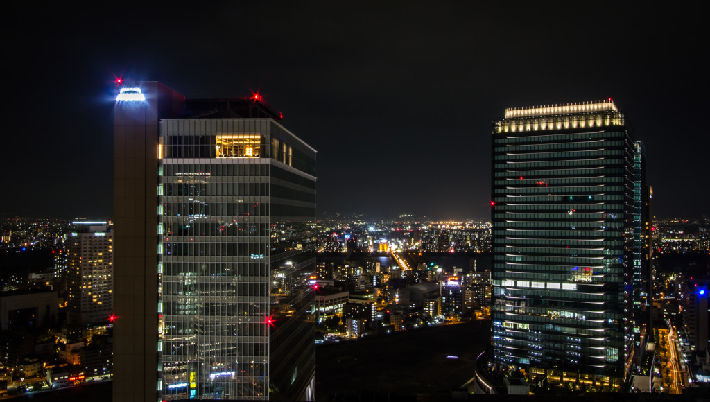 Twin buildings pictured at night; taken rooftopping in Osaka, Japan