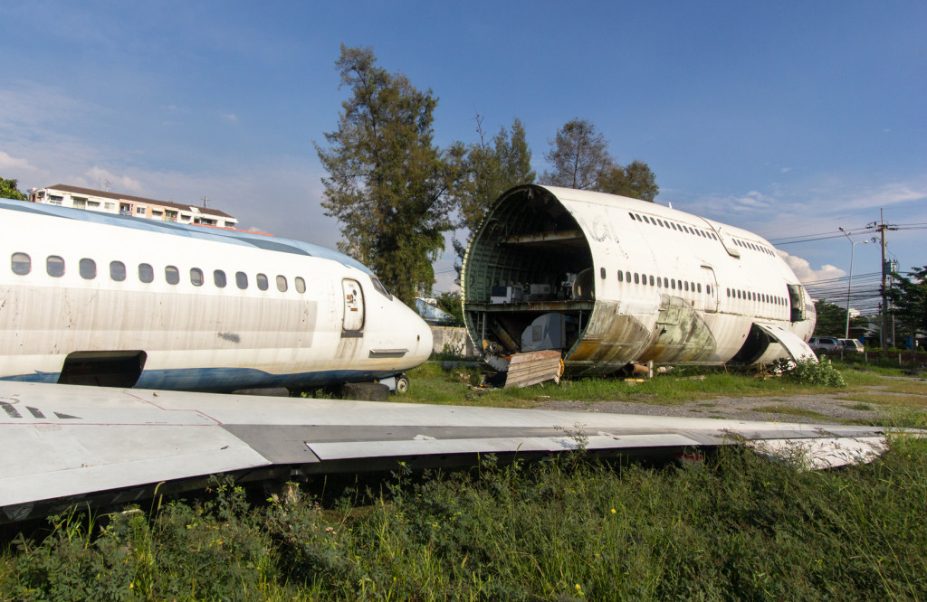 Outdoor view of the rear section of an abandoned 747 aircraft, along with another plane